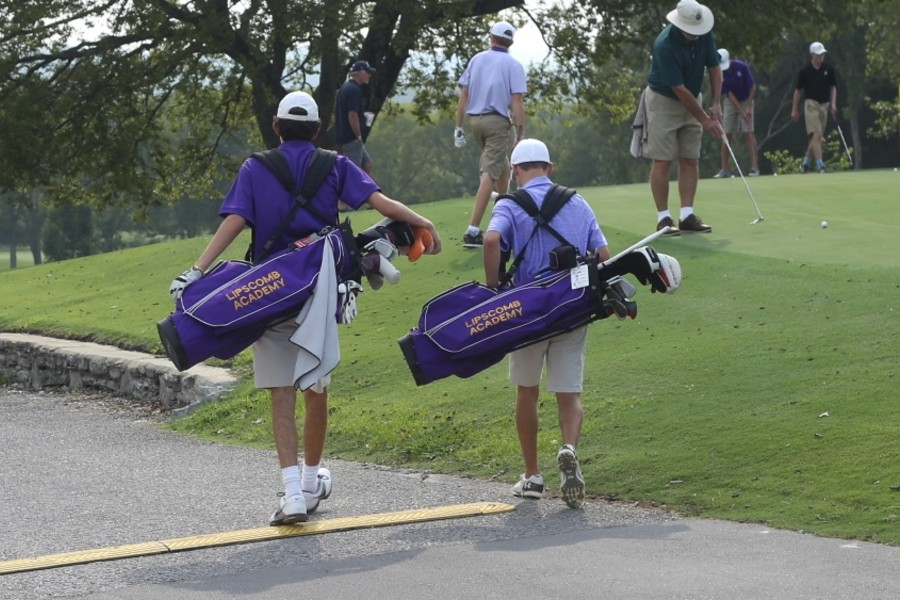 Two golfers carrying Lipscomb Academy golf bags