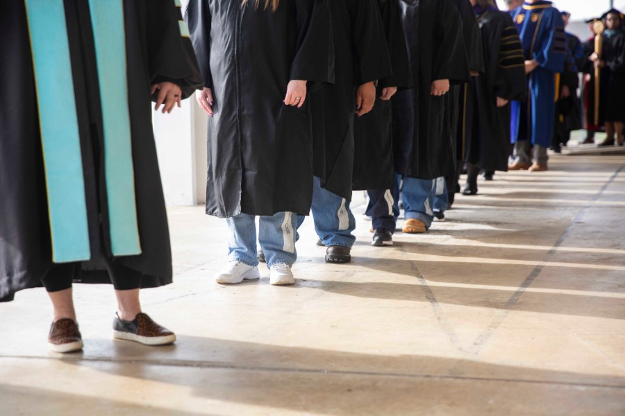 Graduates wearing graduation robes over prison blues.