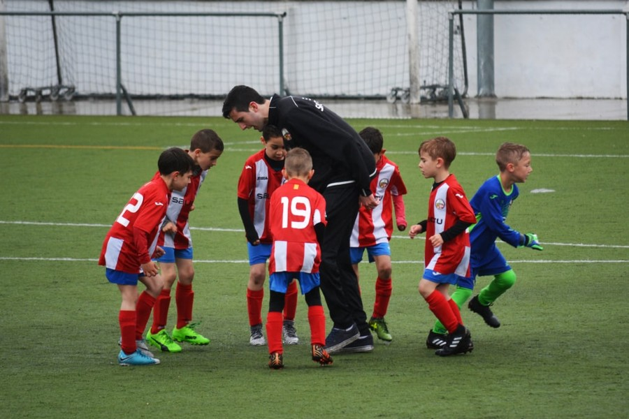 Soccer coach surrounded by group of young players