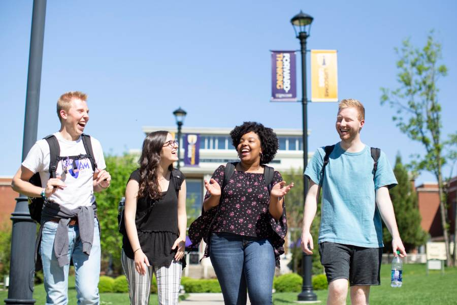 Photo of four students walking on campus