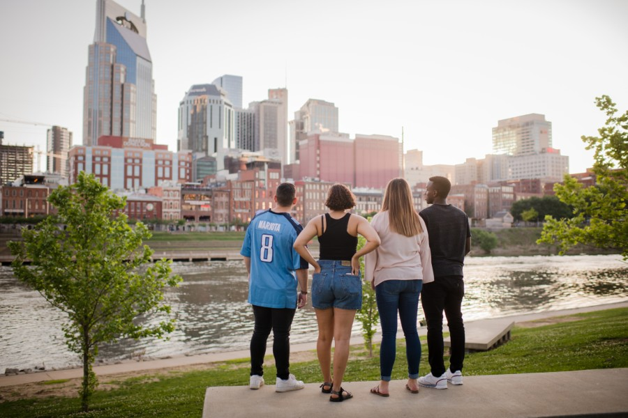 Tourists standing on riverfront looking at Nashville skyline.