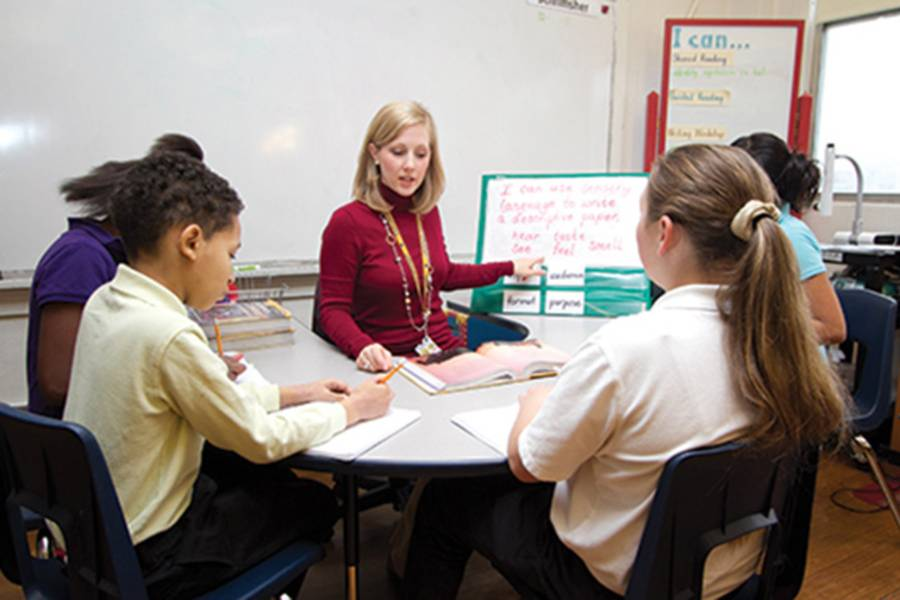 Female teacher sitting at table with elementary school students