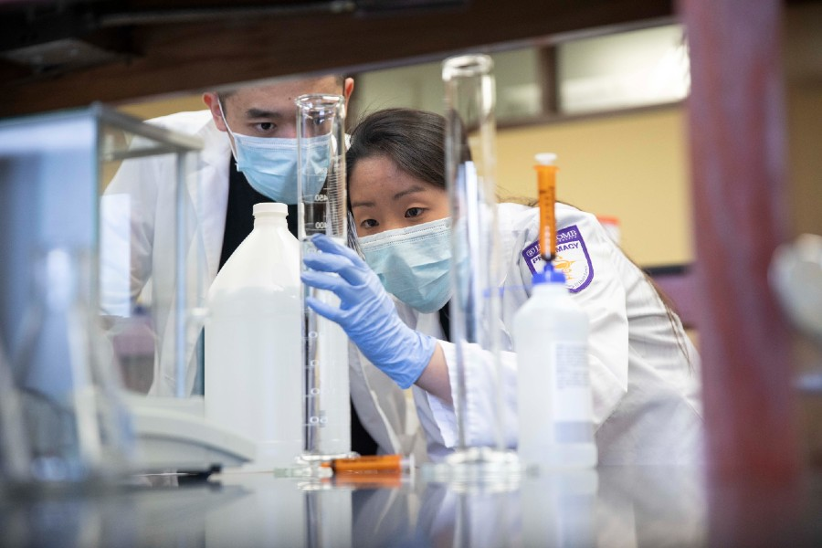 Two students compounding head sanitizer