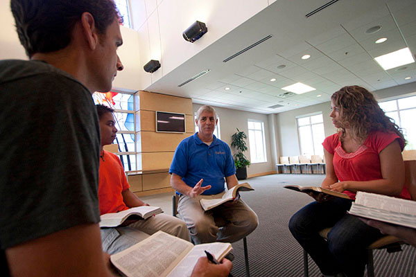 A professor leads students with their Bibles open in a discussion through Scripture