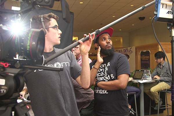 A student surrounded by film equipment holds a boom mic over a shot being recorded