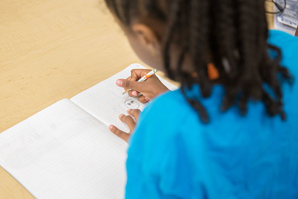 A child draws an image in a composition notebook