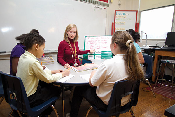 A teacher sits across from four students instructing them on how to write well