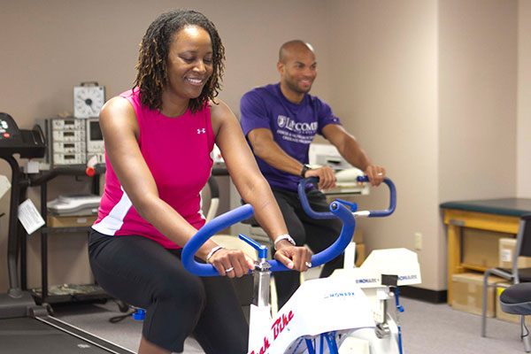 A woman and a man ride exercise bikes in a fitness room