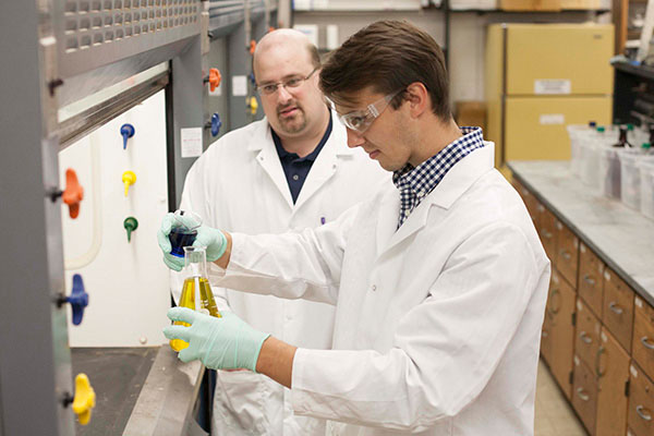 A professor observes as a student in a lab coat prepares to mix two chemicals in a flask