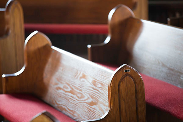 Two wooden pews with red seat cushions