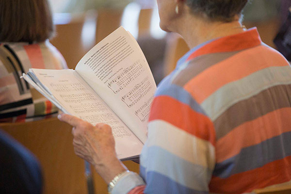 A church member faces toward the pulpit while reading from a hymnal