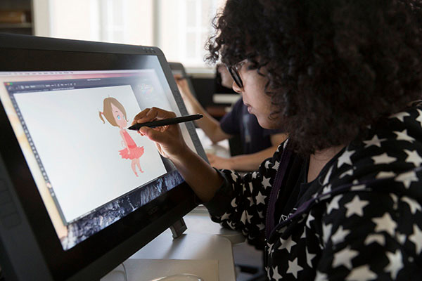 A female student draws a young brunette ballerina character on a tablet