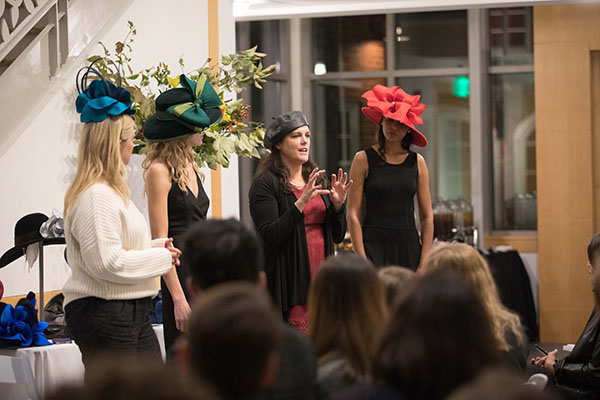 A designer explains some of her hat designs at a fashion show