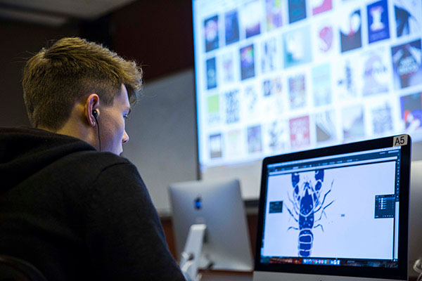 A student working on a desktop uses Adobe Illustrator to craft a logo of a lobster