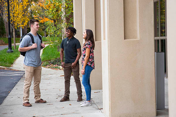 Three students stand outside talking
