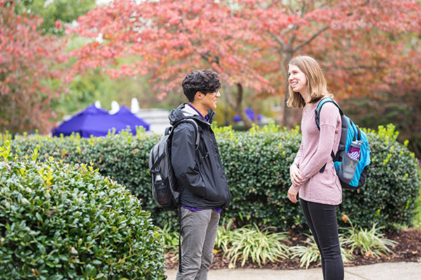 Two students stand outside talking