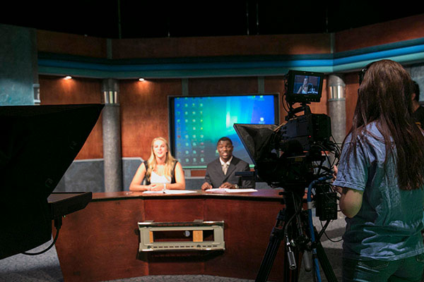 A woman stands behind a camera recording two newscasters at a desk