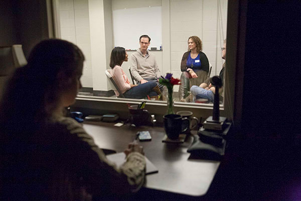 A student observes from a separate room discussion between patients and a psychologists