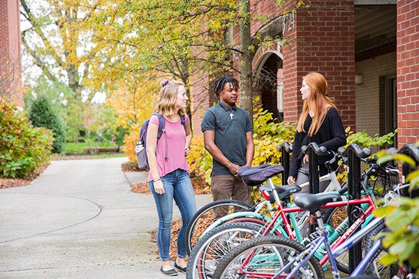 Three students standing outside and talking to one another