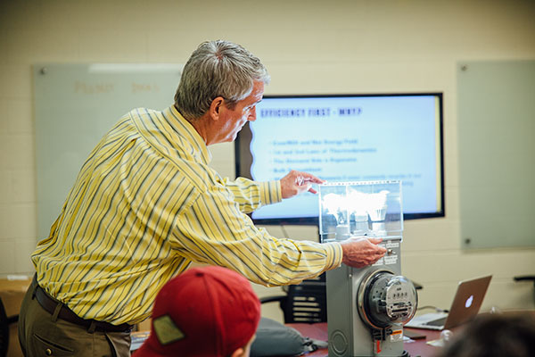A professor conducts an experiment during his lecture with lightbulbs and an electric meter