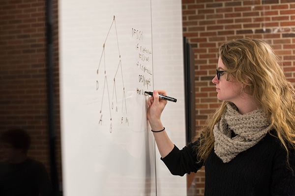 A female student uses a whiteboard to solve a problem