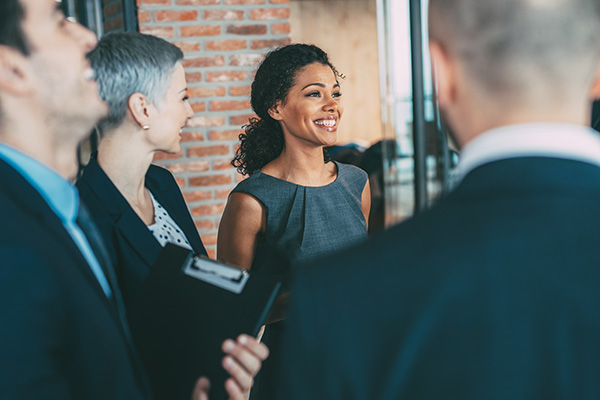 A woman stands smiling amongst a small group of clients