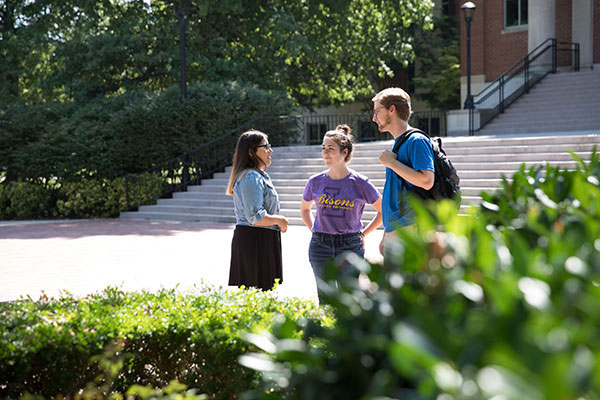 Three students standing outside and talking