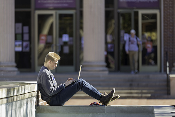 A student sits outside while completing work on his laptop