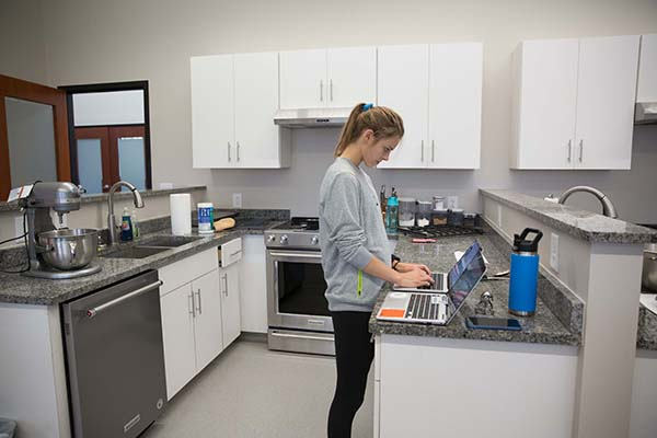 A student works on an assignment on her laptop in the nutrition lab