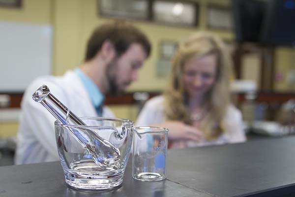 A beaker, mortar and pestle sit on a lab bench while two students conduct an experiment in the background