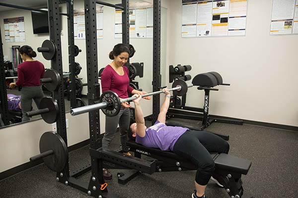 One student spots another student as she lifts a barbell