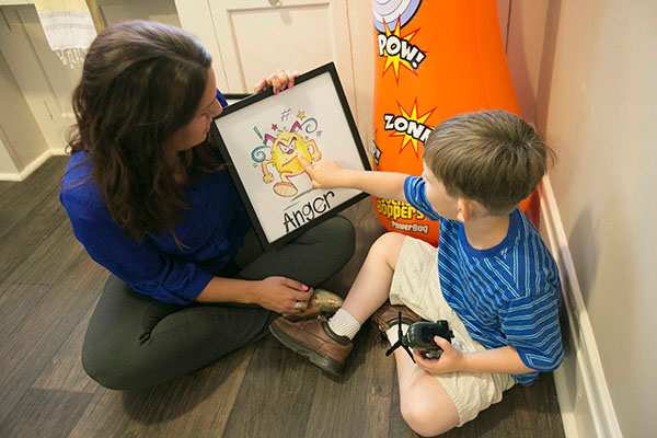 A woman sits on the floor with a young boy that points to an emotion on a chart held by the woman