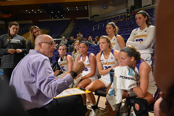 A coach talks to eight of his athletes in the middle of a timeout