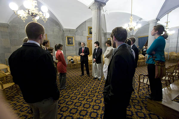 A group of students stand in a parliament building and listen to a man talk