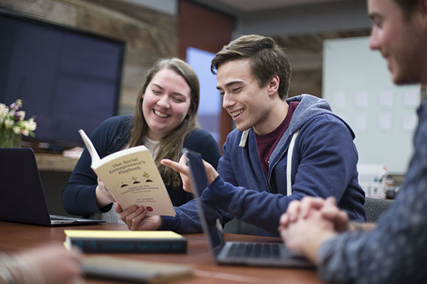 "Two students read through their textbook titled ""The Social Entrepreneur's Playbook"""