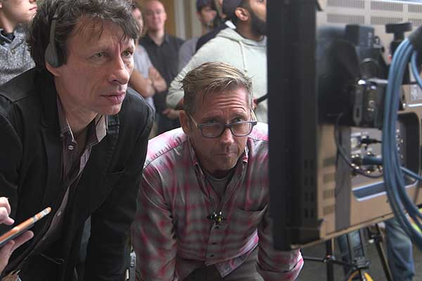 Two professors observe the work of some of the film students on a monitor