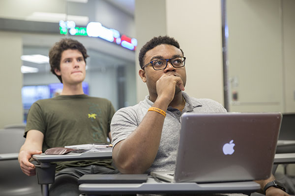 Two students sitting in classroom looking towards front of the room.