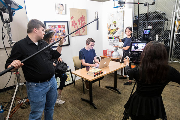 Students work together on creating a film with boom, video camera and more.