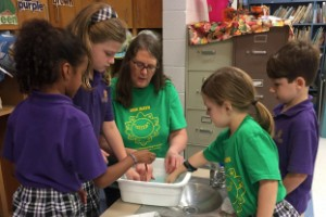 Four young students working on science project with teacher.