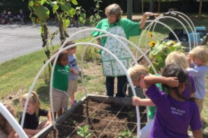 Young students take care of a garden located outside the school building.