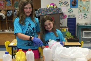 Two female elementary students sorting plastic water jugs.