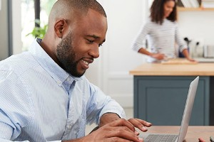 African American man sitting at table with laptop computer