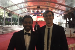 Two students in suits standing on the red carpet at Cannes.
