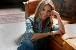Sheryl Crow sitting in chair.