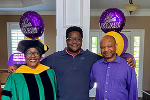 Carl Mhlanga with his parents at a graduation party