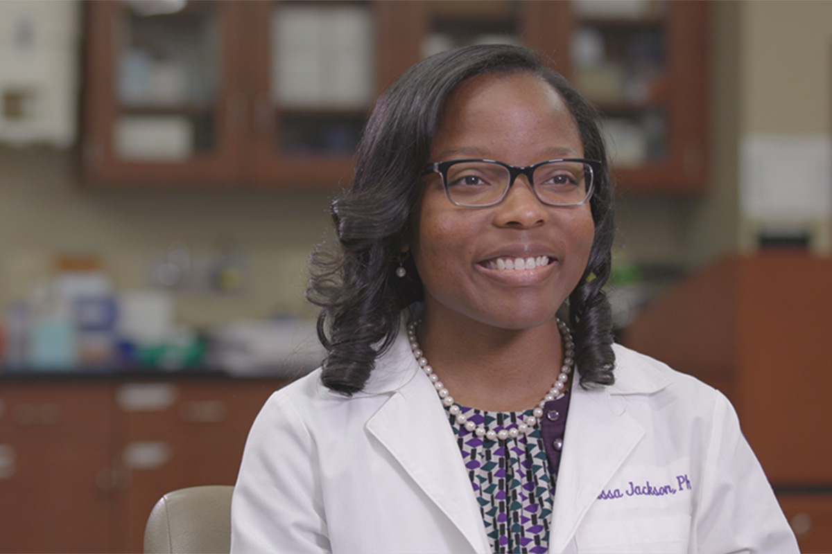 Klarissa Jackson in lab coat sitting in a lab on Lipscomb's campus.