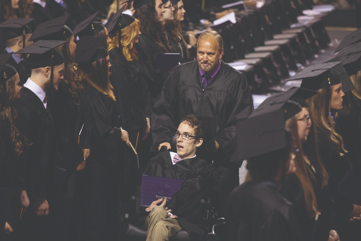 Seth Walker and Ken Brassell walk back to their seats after receiving diplomas