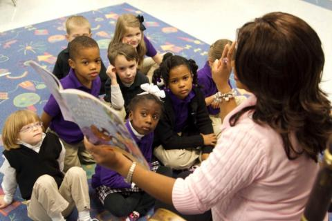 Teacher reads book to group of elementary school children.