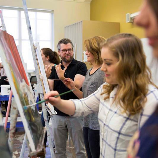 Art professor instructs students on painting techniques.