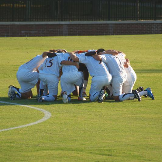 Men's soccer team huddles for prayer before a game.